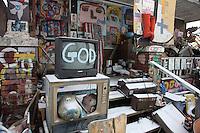 televisore con scritta Dio , God, e oggetti di recupero