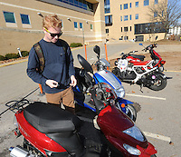 STAFF PHOTO ANDY SHUPE - Lachlan Moore, a junior at the University of Arkansas' Walton College of Business from Australia, prepares to leave  on his scooter Monday, Dec. 15, 2014, on the university campus in Fayetteville. The Fayetteville City Council will consider Tuesday an ordinance requiring scooter drivers to secure liability insurance for their vehicles.