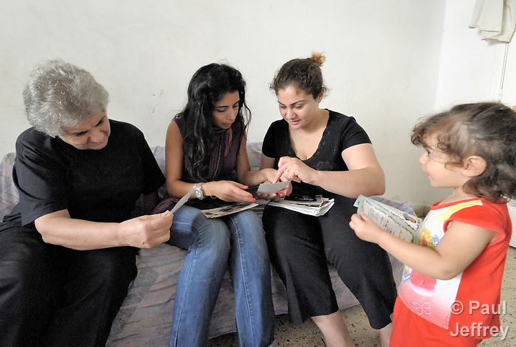 Rana Ramzi (second from right) shows photos of her dead husband to Ranha Chehab, a social worker of the Caritas Lebanon Migrant Center, in Ramzi's apartment in Beirut. Ramzi's husband was killed February 29, 2008, in Mosul, Iraq, while working as a driver and assistant to the Chaldean archbishop of Mosul, Archbishop Faraj Rahho, who was later found dead. Ramzi and her three children (including Farah, right) fled Iraq in May and live as refugees in Lebanon, along with Ramzi's mother (left), also a refugee from Iraq. They have received assistance from the Caritas Lebanon Migrant Center, which is funded by Catholic Relief Services, the relief and development agency of the U.S. Catholic community. Both Ramzi and her children and mother hope to resettle in the United States.