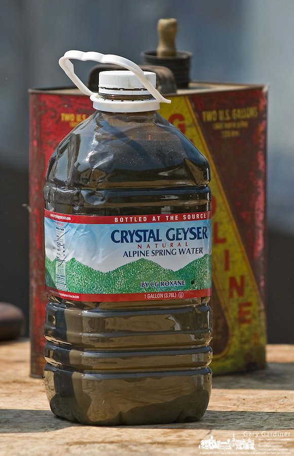 A plastic bottle originally filled with water now holds used motor oil. The bottle was among the bottles and cans of leftover household chemicals and cleaners dropped off at a hazardous waste disposal site in Westerville, Ohio. Homeowners were able to remove any hazardous waste from their homes to be properly recycled or disposed of instead of placing in their trash or pouring down the drain.<br />
