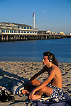 Man listening to music on headphones on sand beach in front of Stearns Wharf, Santa Barbara, Southern Coast, California