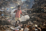 A boy scavenges for recyclable items in the smoldering municipal garbage dump in Chennai, India. He and other boys who work in the dump spend their nights safely in a shelter sponsored by the Madras Christian Council of Social Service.