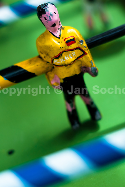 A table football player figure, with a painted yellow shirt, is seen inside the table football box on the street of Pesillo, a small village in the mountains of Ecuador, 26 June 2010. Table football, also known as futbolin in Latin America, is a widely popular table-top game in Ecuador. During the annual fairs, the rusty old outdoor-designed tables, fully ocuppied by excited children, may be found on all public places, particularly on the squares and in the parks. Human players use figures mounted on rotating bars to kick the small plastic ball into the opposing goal. Each team of 1 or 2 human players controls 4 rows on its side of the table. The game ends when one team scores a predetermined number of goals. In 2002, the International Table Soccer Federation (ITSF) was established to promote the sport of table football.
