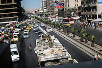 An armoured vehicle carrying government troops drives through central Damascus.