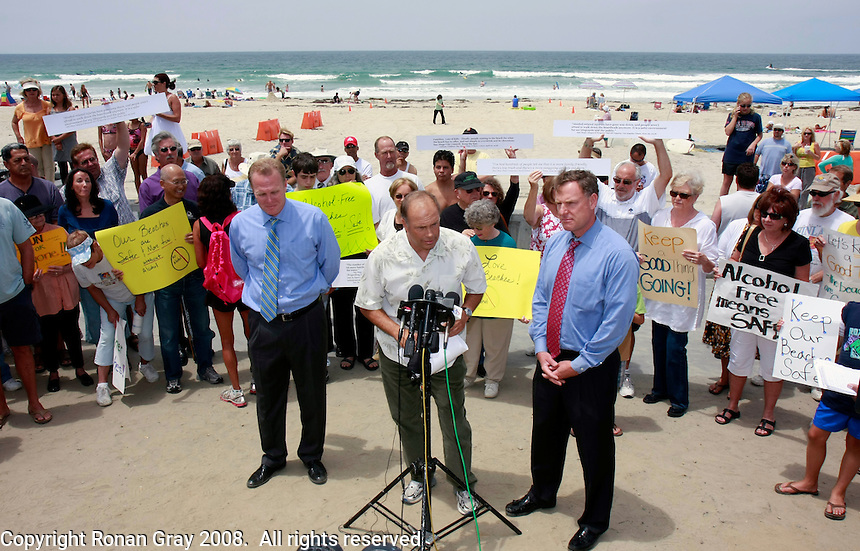 Local business owner Randy XXXX is flanked by Council Member Kevin Faulconer and Council President Scott Peters at a press conference in Mission Beach Tuesday, July 22rd 2008.  Peters and Faulconner called the conference to announce that they will bring a proposal to put the beach alcohol ban on the November Ballot before the council at the next meeting.  Residents, business owners and media attended the rally with the overwhelming majority apparently in favor of the alcohol ban.
