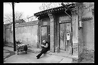 A cleaning lady checks her mobile phone as she sits in front of a traditional courtyard house at an old hutong, or alleyway, in Beijing, China, January 2014. The old and traditional residential hutongs are vanishing rapidly to make way for the redevelopment of Beijing.