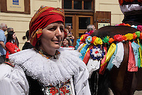 Headshot of woman participating in the ride of kings in Prague, wearing a traditional Moravian costume.<br /> <br /> Twelve-year-old Frantisek Libosvar dressed as a girl and with a rose in his mouth leads the royal procession during Ride of the Kings as part of Navalis Celebrations on May 15, 2015 in Prague, Czech Republic. The Navalis Saint John's celebrations take place to commemorate Czech saint and Prague native, Saint John of Nepomuk, patron of all people of the water. <br /> <br /> <br /> The Ride of the Kings takes place during the spring, as a part of the Pentecost traditions . A group of young men ride through a Prague in a ceremonial procession. The ride is headed by chanters, followed by pageboys with unsheathed sabres who guard the King &ndash; a young boy with his face partially covered, holding a rose in his mouth &ndash; and the rest of the royal cavalcade. The King and pageboys are dressed in women&rsquo;s ceremonial costumes, while the other riders are dressed as men. The entourage rides on decorated horses, stopping to chant short rhymes that comment humorously on the character and conduct of spectators. The chanters receive donations for their performance, placed either in a money box or directly into the riders&rsquo; boots. The King&rsquo;s retinue returns home after a few hours of riding, and celebrates in the evening at the house of the King with a small feast, music and dancing. The practices and responsibilities of the Ride of the Kings are transmitted from generation to generation. The traditional paper decorations for the horses and the ceremonial costumes, in particular, are made by women and girls familiar with the processes, colour patterns and shapes specific to each village.