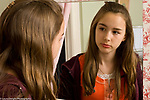 Teenage girl age 13 in bedroom looking at self in mirror concerned about appearance