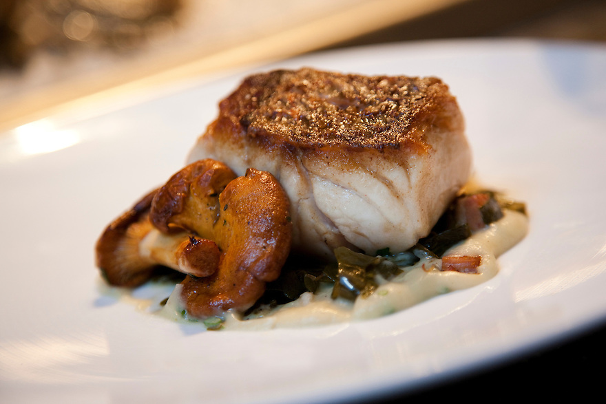 A plate at Black Salt Restaurant in Washington DC, a popular dining spot near the Potomac River in the Palisades neighborhood.   The plate is American red snapper fish with chanterelles and bacon braised greens..