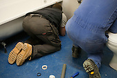 Plumbing students working on a difficult to reach spot, Able Skills, Dartford, Kent.