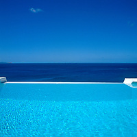 The cool blue of an infinity pool appears to flow into the deep blue of the ocean beyond