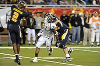26 December 2010:  FIU linebacker Jarvis Wilson (31) is held by Toledo offensive lineman Mike VanDerMeulen (74) while rushing the quarter in the second half as the FIU Golden Panthers defeated the University of Toledo Rockets, 34-32, to win the 2010 Little Caesars Pizza Bowl at Ford Field in Detroit, Michigan.