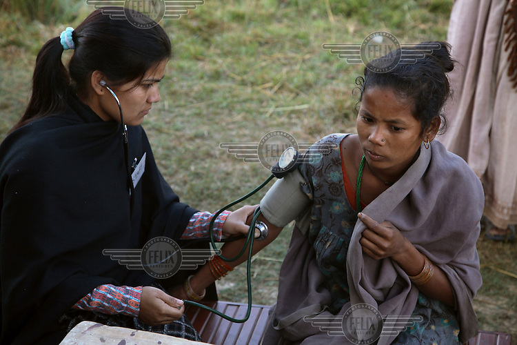 Medical staff check a patient's blood pressure during an annual sterilisation event managed by a visiting medical NGO at a rural health post.