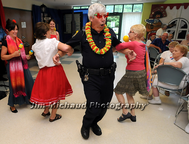 2nd Place Winner New England Region by the National Press Photographers Assc Clip Contest<br /> <br /> South Windsor Police Officer Jim Morrison, really gets into it as he dances the Mexican Hat Dance with Mickey Kozikowski, left, and Irene Murray,  as they perform for seniors at South Windsor Senior Center, Tuesday, July 22, 2008. The event was the Where in the World? International Senior Pinic, which included a breakfeat, games from a round the world and music by Jon Banker. (Jim Michaud/Journal Inquirer)