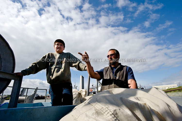 8/4/2008--Dillingham, AK, USA..Native Alaskans Steven Shade, 50 (right), his son August, 11 (left) unload nets from Shade's fishing boat in Dillingham Port. Like many fisherman in the region, Shade opposes the proposed Pebble mine..The Pebble Mine site is currently being drilled to map deposits of ore for possible extraction. The mine contains large deposits of copper, gold, and molybdenum and is in the Bristol Bay region of Southwest Alaska, near Lake Iliamna. The proposal to build a large mine is controversial and opponents say it threatens nearby wild salmon runs from Bristol Bay into the nearby watersheds. .The mine is being explored by Pebble Ltd Partnership, a joint venture of  Northern Dynasty Partnership and Anglo American US LLC. The mine  would probably include an open pit and large dams to contain waste. Bristol Bay is home to some of the largest runs of salmon in the world and the world's largest sockeye salmon fishery. It's also a popular sport fishing area, and subsistence fishing is important to the region's native communities...©2008 Stuart Isett. All rights reserved.