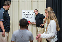 NWA Democrat-Gazette/BEN GOFF @NWABENGOFF<br /> Haem Mea, 9, of Springdale reads an eye chart with optometrist Dr. David Hurd (from left), optician Rick Rakotz and intern Sydney Maczko from Vold Vision Saturday, Aug. 10, 2019, during the Northwest Arkansas Community Back to School Extravaganza at the Yvonne Richardson Community Center in Fayetteville. Four area churches; St. James Missionary Baptist Church, Good Shepherd Lutheran Church, Agape Ministries and New Heights, partnered to put on the event. Community partners provided free vision and dental screenings, haircuts, blood pressure checks for parents and backpacks full of school supplies. Vold Vision offered free vision screenings for children at the event.