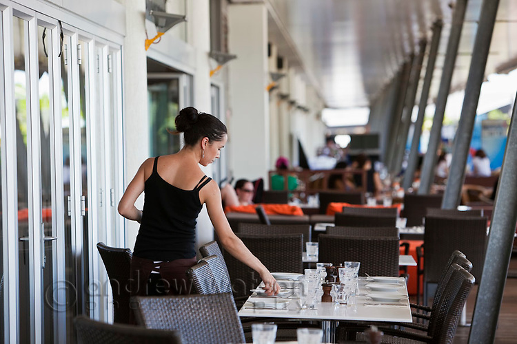 Waitress setting table at a waterfront restaurant.  The Pier, Cairns, Queensland, Australia