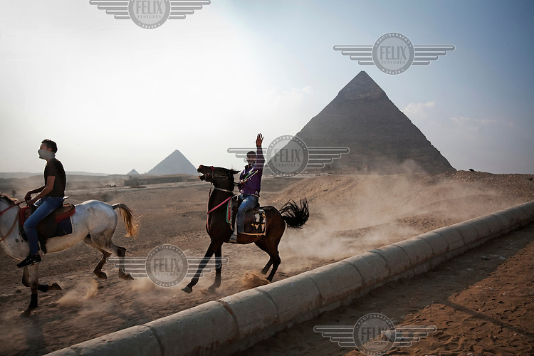 Egyptian tourists ride horses beside the Pyramids of Giza