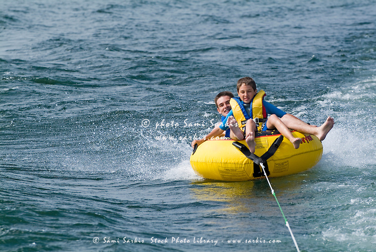 Two boys riding an inflatable seabiscuit in the sea, Biscarrosse, France.