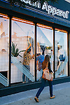 A woman walks past as Visual Manager Will Gomez (in blue) and Visual Display Assistant Jacob Estevez design and decorate the window display at the American Apparel store located on Sunset Boulevard in the Echo Park neighborhood of Los Angeles, California February 6, 2015.