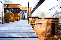 A weathered footbridge leads to the entrance door which is located at the top of this contemporary tree house