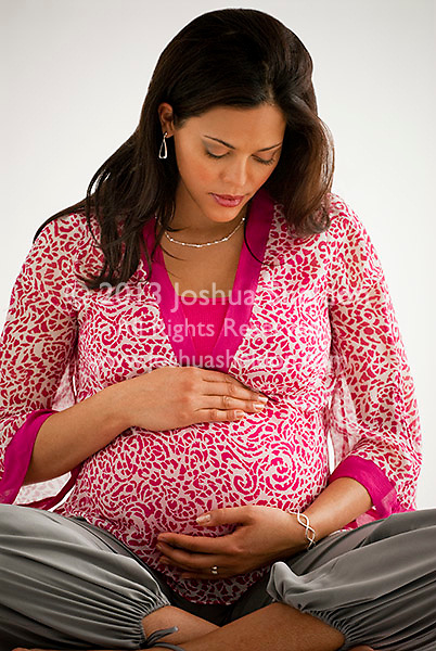 Pregnant Hispanic woman, sitting down, hands on stomach
