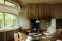 An Arco lamp and Warren Platner chairs sit in front of the brick and concrete fireplace in the living room.