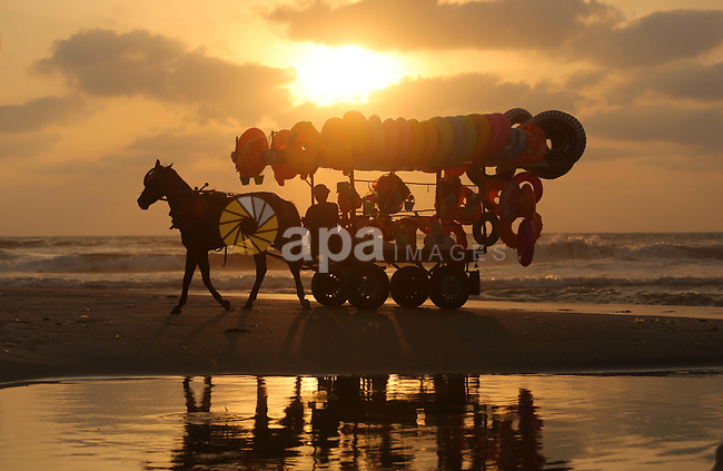 A Palestinian vendor rides his horse cart on the beach of Gaza city, on July 5, 2017. An immediate consequence of the electricity cuts has been suffering for Gazans. A new U.N. report said Gaza gets electricity just four to six hours a day, and 29 million gallons of sewage is flooding into the Mediterranean Sea every day and threatening to overflow into the streets. Photo by Ashraf Amra