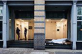 A homeless man sleeping in the doorway of an office building close to Old Street roundabout in Shoreditch, London, a run-down commercial district  also known as Silicon Roundabout, which is undergoing gentrification as it becomes a centre for web-based companies and IT start-ups.