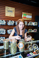 Budtender Jasmine Maimone (cq) behind the counter at a LiveGreen Cannabis store in Denver, Colorado, Monday, July 21, 2014. <br /> <br /> Photo by Matt Nager
