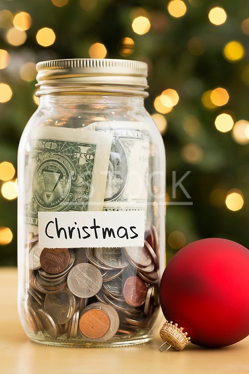 Jar filled with money labeled Christmas and Christmas ornaments lying beside