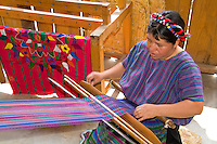 Woman at loom weaving artwork fabrics by hand in colorful dress in San Antonio on remote Lake Atitlan in Guatemal