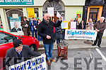 Michael Pixie O'Gorman of Right to Water burns his water bill outside John Brassils office in Ashe Street on Monday.