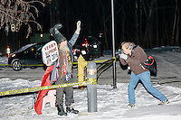A news photographer takes pictures as Satirical presidential candidate Vermin Supreme protests his exclusion from the Lesser-Known Candidates Debate outside Saint Anselm College's New Hampshire Institute of Politics in Goffstown, New Hampshire. Supreme participated in previous debates, but was told he would be not allowed back this year because of an incident during the 2011 debate in which Supreme threw glitter on candidate Randall Terry. The college put up police tape behind which the candidate was told to stand without risking arrest. Supreme's platform advocates a pony-based economy, using zombies to solve the energy crisis, and other outlandish ideas. Supreme has been on the New Hampshire primary ballot in 2008 and 2012, though he has began running for president in 1992.