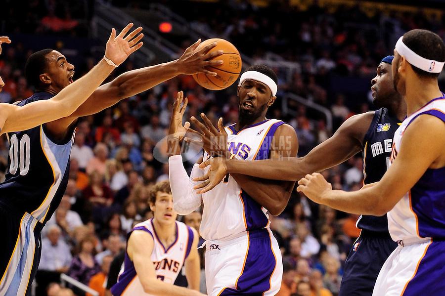 Dec. 8, 2010; Phoenix, AZ, USA; Phoenix Suns forwas Hakim Warrick (center) reacts as Memphis Grizzlies forward (00) Darrell Arthur reaches for a rebound in the first half at the US Airways Center. Mandatory Credit: Mark J. Rebilas-