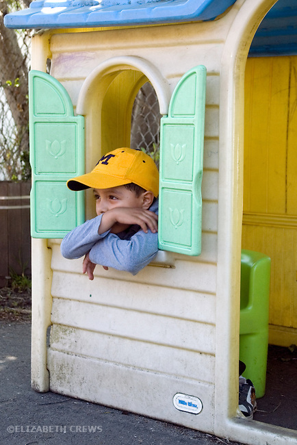Berkeley CA  Boy reflecting on playground from his station instide playhouse at preschool.