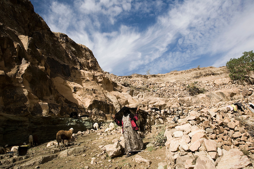 Yemen - Sana'a - Old jewish quarter in the outskirst of the capital. Most of the inhabitants of this area cannot afford to buy water so they walk 2 hours to reach the closest water well. Myriam, 15 years old is getting ready, covering up, to go and collect water.Yemen's economy depends heavily on oil production, and its government receives the vast majority of its revenue from oil taxes. Yet analysts predict that the country's petroleum output, which has declined over the last seven years, will fall to zero by 2017. The government has done little to plan for its post-oil future. Yemen's population, already the poorest on the Arabian peninsula and with an unemployment rate of 35%, is expected to double by 2035..The trends will exacerbate large and growing environmental problems, including the exhaustion of Yemen's groundwater resources. Given that a full 90% of the country's water is used for agriculture, this trend portends disaster..Sanaa's well are expected to dry out by 2015, partly due to illegal drilling, partly because 40% of the city's water is diverted for qat production, and partly because conservation rules are difficult to enforce. Only 20% of the houses receive water, the other 80% has to collect it from pumps and wells. 15% of the urban population only uses bottled water as its primary drinking water source and that is why Yemen has one of the highest world mortality rate, most of the diseases being related to water..