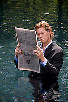 Young man wearing suit reading business section of newspaper while standing in water