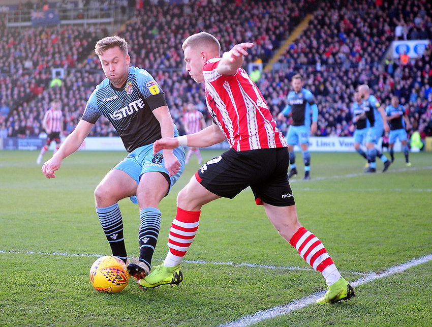 Lincoln City's Danny Rowe vies for possession with Stevenage's Joel Byrom<br /> <br /> Photographer Andrew Vaughan/CameraSport<br /> <br /> The EFL Sky Bet League Two - Lincoln City v Stevenage - Saturday 16th February 2019 - Sincil Bank - Lincoln<br /> <br /> World Copyright © 2019 CameraSport. All rights reserved. 43 Linden Ave. Countesthorpe. Leicester. England. LE8 5PG - Tel: +44 (0) 116 277 4147 - admin@camerasport.com - www.camerasport.com