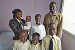 Jacob Tung, a refugee from South Sudan, with his six children in their apartment in Cairo, Egypt. Except for the baby, his children attend classes in a school operated by St. Andrew's Refugee Services, which is supported by Church World Service. Tung's wife is not pictured.