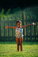 Portrait of young African-American girl smiling with arms outstretched and standing in her swimsuit enjoying a sprinkler.