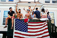 People drink alcohol on a porch during St. Peter's Fiesta in Gloucester, Massachusetts, USA.