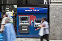 Pedestrians walk by a Capital One Bank ATM in the New York City borough of Manhattan, NY, Monday May 12, 2014. Capital One Financial Corporation is a U.S.-based bank holding company specializing in credit cards, home loans, auto loans, banking and savings products.