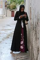 Zanzibar, Tanzania.  Zanzibari Lady in a Buibui Checking her Cell Phone.