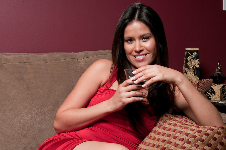 Young hispanic woman relaxing at home with a glass of wine.