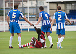 Hartlepool United defenders Sam Collins, Simon Walton and Neil Austin offering a helping hand to visiting forward Marvin Emnes during the first-half at the Victoria Ground, Hartlepool, during a pre-season friendly between the home team and Middlesbrough. Hartlepool were relegated to League Two at the end of the 2012-13 season whilst their Teesside neighbours remained two divisions above them in the Championship. The game ended in a no-score draw, the home team's goalkeeper Scott Flinders saving a second-half penalty from Boro's Lucas Jutkiewicz, watched by a crowd of 2307.