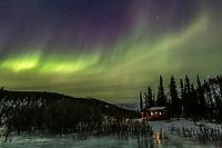 Aurora borealis swirls over Windy Gap cabin in the White Mountains National recreation area in interior Alaska.