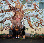 Three guys hanging around a mural painted on the side of a building in downtown Estacada, Oregon