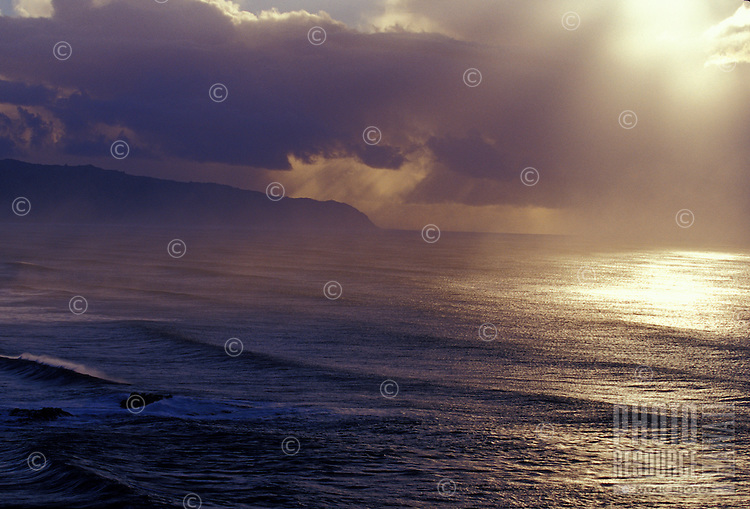 Late afternoon sun on large swell amid rainsqualls seen from heiau over Waimea Bay, North Shore, Oahu, Hawaii