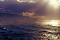 Late afternoon sun on large swell amid rainsqualls seen from heiau over Waimea Bay, North Shore, Oahu, Hawaii